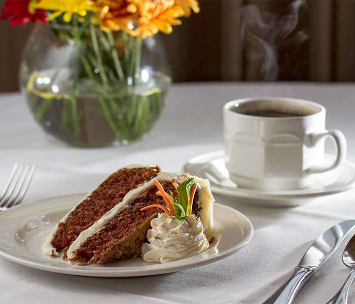Carrot cake and coffee at a finely appointed table